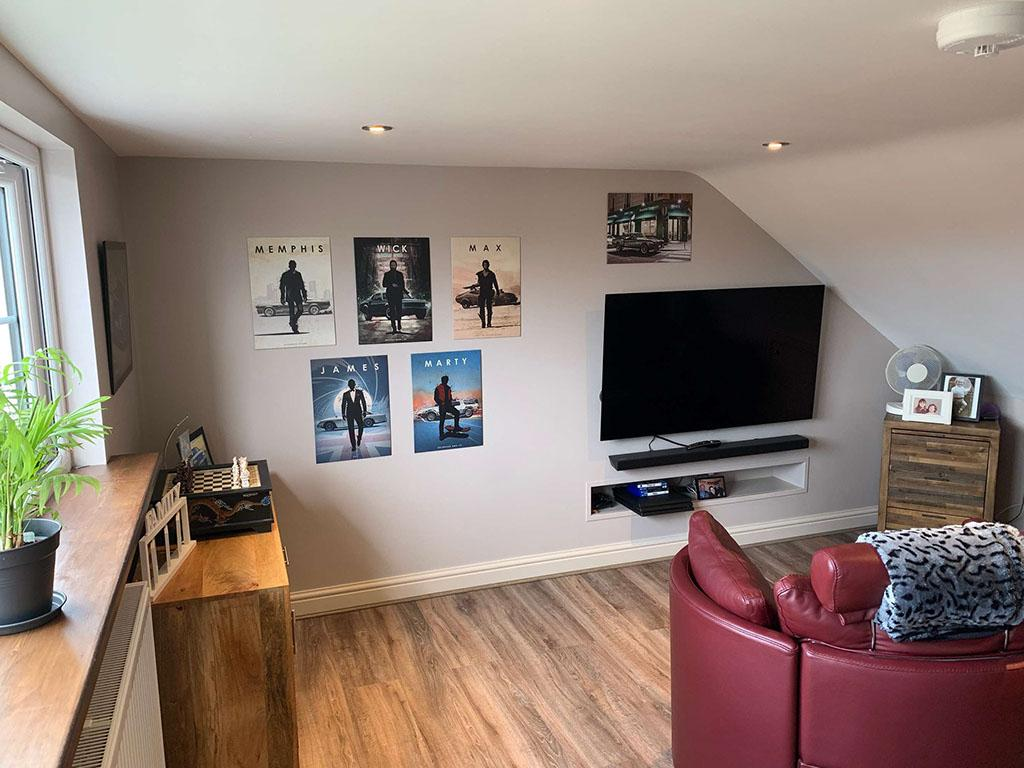 Loft conversion into a bedroom with posters on the wall